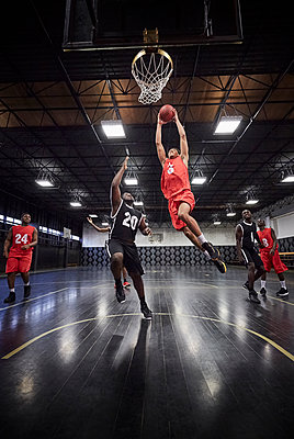 Young male basketball player jumping to slam dunk basketball in game on court in gymnasium - p1023m1486388 by Chris Ryan