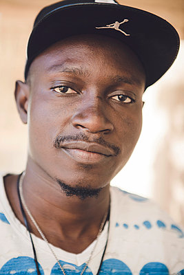 Dark-skinned man wearing basecap - p1150m1514975 by Elise Ortiou Campion