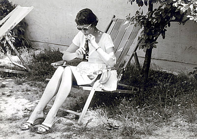 Young woman in canvas chair reading newspaper - p1541m2116891 by Ruth Botzenhardt