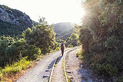 Greece, Pilion, Milies, back view of man walking along rails of Narrow Gauge Railway - p300m1580837 von Maria Maar