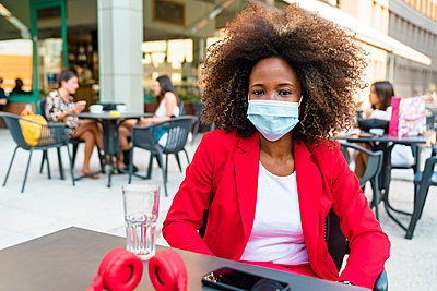 Woman wearing protective face mask sitting at sidewalk cafe - p300m2221569 by Giorgio Magini