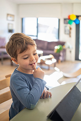 Boy using digital tablet during online class at home - p300m2252552 by Ignacio Ferrándiz Roig
