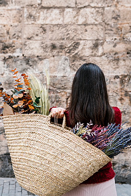 Young woman holding bag with flowers standing in front of wall - p300m2274947 by Ezequiel Giménez
