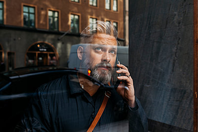 Man on smart phone through window in Sweden - p352m1536749 by Folio Images