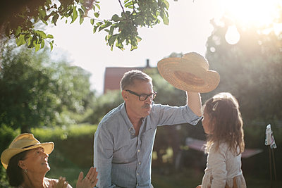 Woman clapping and looking at senior man holding straw hat over granddaughter in backyard during sunny day - p426m2036654 by Maskot