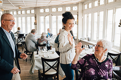 Senior friends giving high-five in restaurant - p426m2149146 by Maskot
