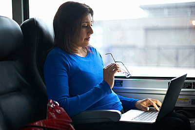Woman travelling on train using laptop - p429m1417883 by Peter Muller