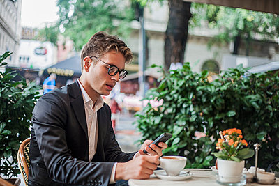 Man using cellphone while having morning coffee at outdoor cafe, Budapest, Hungary - p429m2019475 by Seb Oliver