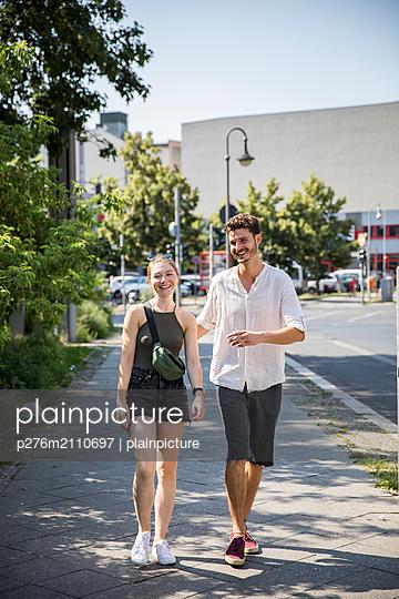 Happy couple is walking on sidewalk - p276m2110697 by plainpicture