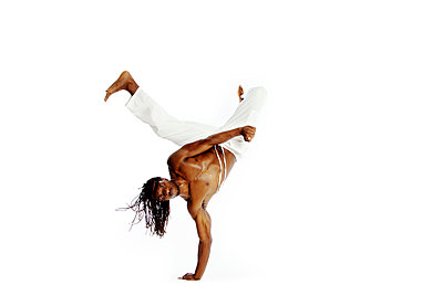 Portrait of man doing handstand against white background - p1166m969832f by Cavan Images
