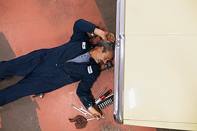 Overhead view mechanic reaching for tool underneath car - p1192m1063903f by Hero Images