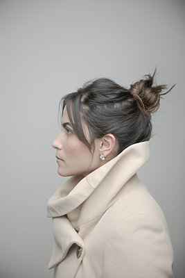 Profile portrait beautiful young brunette Latina woman in coat looking away - p1192m2066369 by Hero Images