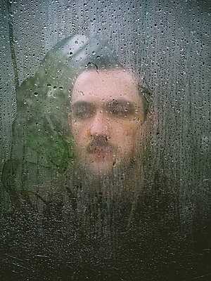 Man behind windowpane, portrait - p1267m2184959 by Wolf Meier