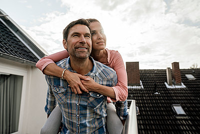 Smiling mature man carrying woman piggyback in balcony against cloudy sky - p300m2243713 by Joseffson