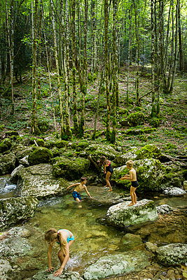 Children are playing on the brookside - p756m2057691 by Bénédicte Lassalle