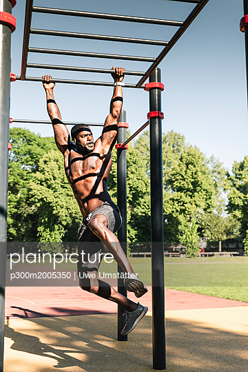 Muscular young man exercising on parcours bars - p300m2005350 von Uwe Umstätter