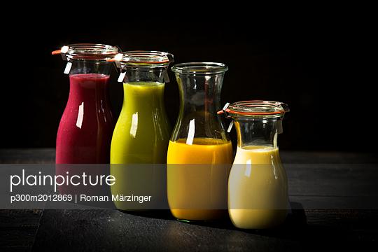 Four glass bottles of different smoothies - p300m2012869 von Roman Märzinger