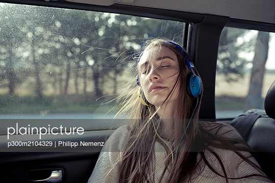 Young woman with windswept hair in a car wearing headphones - p300m2104329 by Philipp Nemenz