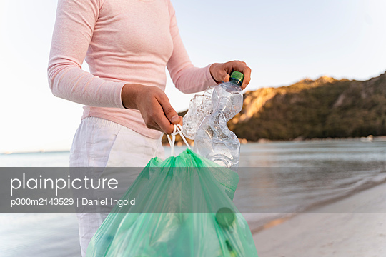 Woman collecting empty plastic bottles  on the beach - p300m2143529 by Daniel Ingold