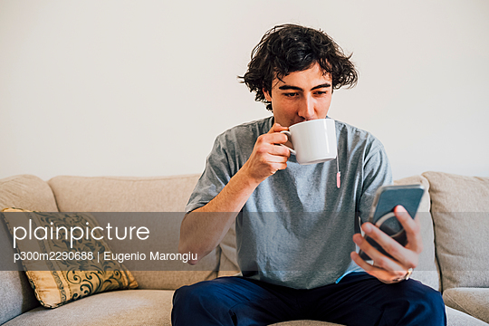Man drinking coffee while using mobile phone at home - p300m2290688 by Eugenio Marongiu
