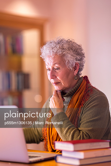 Older mixed race woman using laptop in library - p555m1306135 by Marc Romanelli