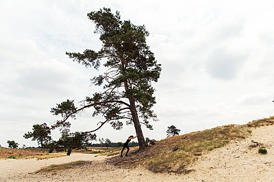 Woman leanging against tree - p1231m2013898 by Iris Loonen