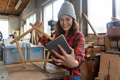 Smiling carpenter holding tablet and workpiece in her workshop - p300m2170700 by Robijn Page
