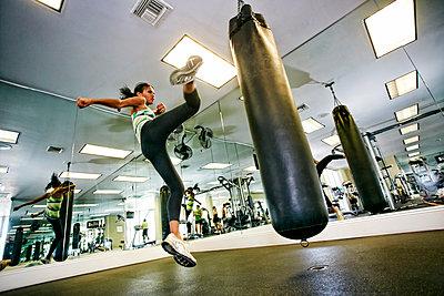 Mixed race woman kicking punching bag in gymnasium - p555m1305527 by Peathegee Inc