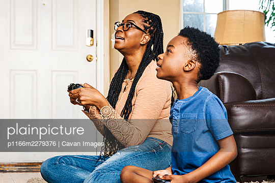 Mother and son playing video game in living room at home - p1166m2279376 by Cavan Images