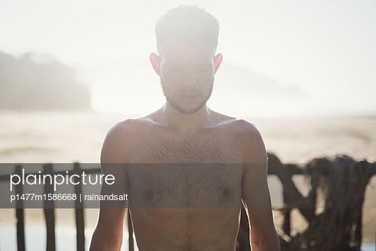Junger Mann mit nacktem Oberkörper am Strand - p1477m1586668 von rainandsalt