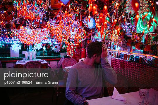 Lonely man in restaurant, colourful illumination, New York City - p1507m2196524 by Emma Grann