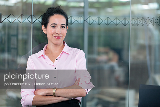 Confident businesswoman standing against glass wall at office - p300m2265197 by Florian Küttler