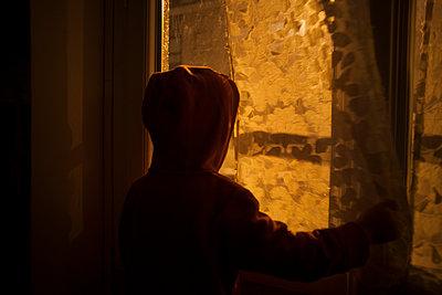 Child looking through window - p1028m1502876 von Jean Marmeisse
