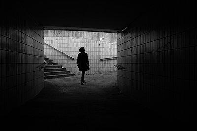 Woman walks in a dark underpass - p1638m2288432 by Macingosh