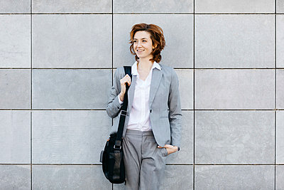 Portrait of a young confident businesswoman in front of wall with gray tiles - p300m2104019 by Josep Rovirosa