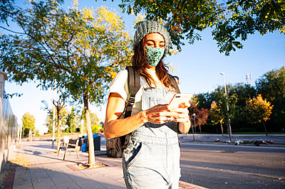 Woman wearing protective face mask using smart phone while walking on footpath during sunny day - p300m2225902 by Jose Luis CARRASCOSA
