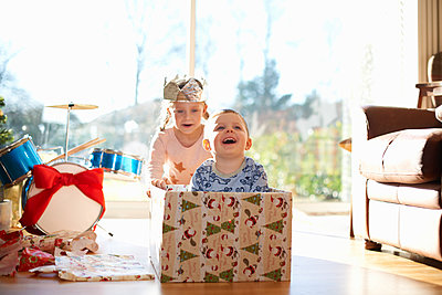 Girl pushing brother in cardboard box at christmas - p429m1226887 by Peter Muller