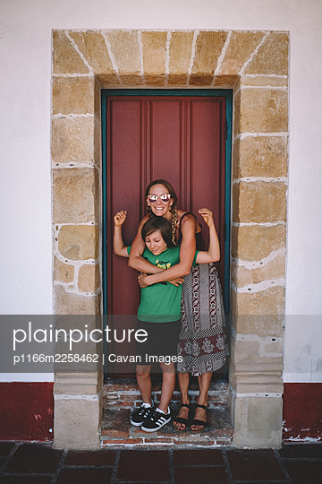 Mom and Son share a hug in an Old Spanish Doorway - p1166m2258462 by Cavan Images