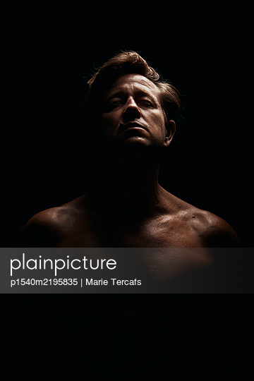 Dramatic portrait of a man on a black background - p1540m2195835 by Marie Tercafs
