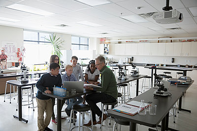 Teacher and middle school students conducting scientific experiment at laptop in science laboratory - p1192m1473268 by Hero Images