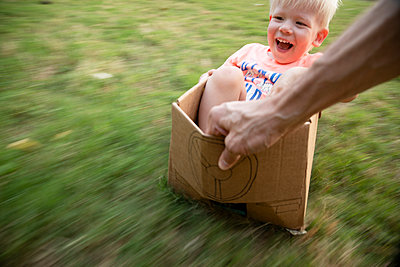 A father pulls his excited son in a cardboard car across their backyard - p1480m2148203 by Brian W. Downs