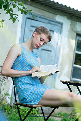 Young woman reading a book in the garden - p427m2134501 by Ralf Mohr