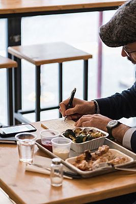 Businessman writing notes over lunch of grilled chicken and vegetables in restaurant - p429m2075450 by Garage Island Crew