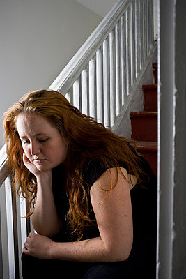 Woman on staircase looking sad - p5350159 by Michelle Gibson