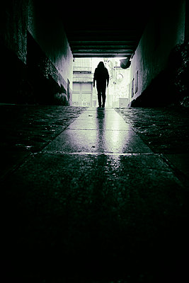 Man in hooded jacket walking out of underground carpark - p597m2142978 by Tim Robinson