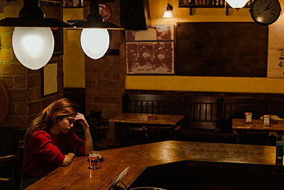Sad woman with beer glass on bar counter sitting in restaurant - p300m2206839 by DREAMSTOCK1982