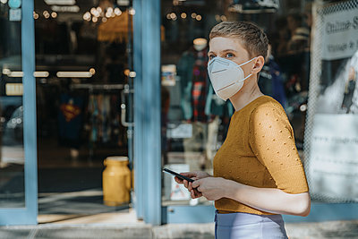Woman wearing protective face mask holding smart phone looking away while standing in city - p300m2226947 by Mareen Fischinger