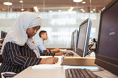Serious female student writing in book while using computer at university library - p426m2072255 by Kentaroo Tryman