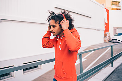 Young man putting on headphones walking past concrete wall - p429m2097977 by Eugenio Marongiu