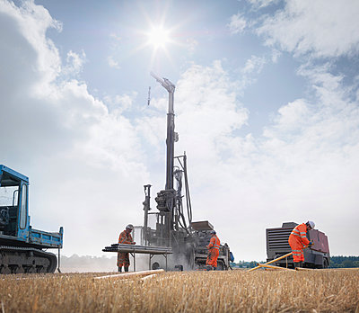 Workers and drilling rig exploring for coal in field - p429m860143f by Monty Rakusen